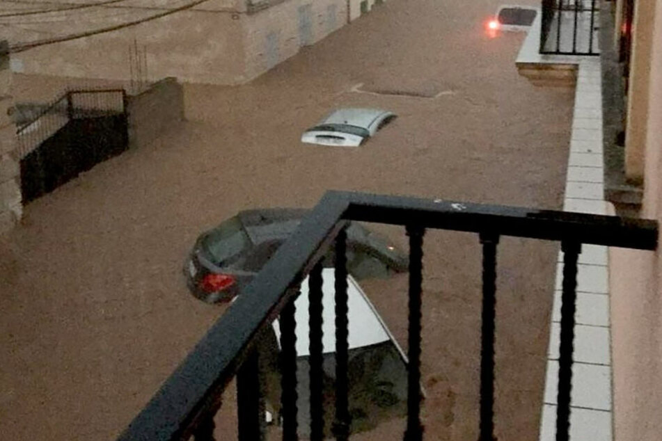 Die heftigen Wassermassen treiben die Autos vor sich her.