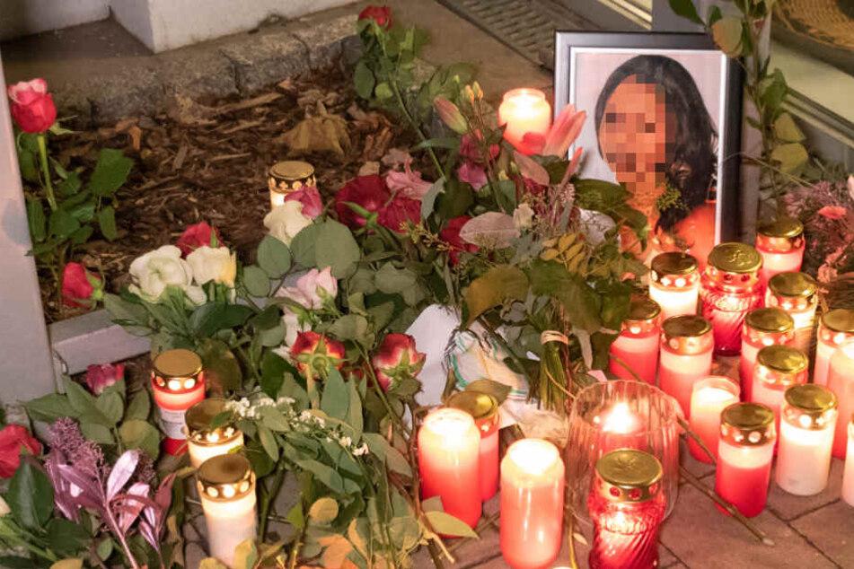 Trauernde haben Blumen neben ein Foto des Opfers gelegt.