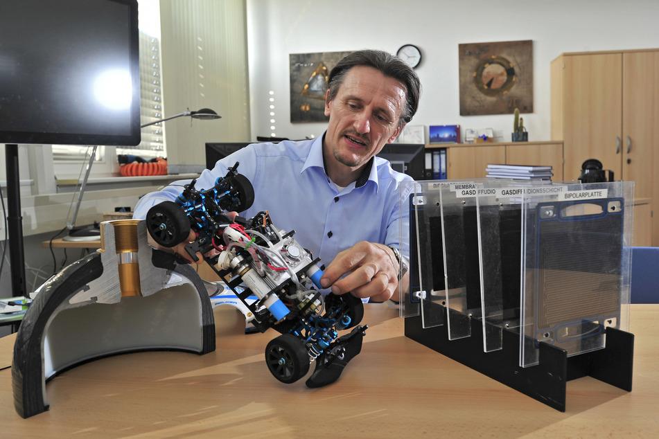 Am Modell-Fahrzeug zeigt Thomas von Unwerth (52), wie ein Wasserstoff-Antrieb im Kleinen aussieht. Links ist das Schnittmodell eines Drucktanks, rechts die fünf Schichten einer Brennstoffzelle zu sehen.