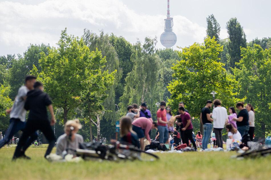 Menschen grillen und genießen das warme Wetter im Volkspark Friedrichshain. Künftig können sich bis zu 100 Personen im Freien treffen.