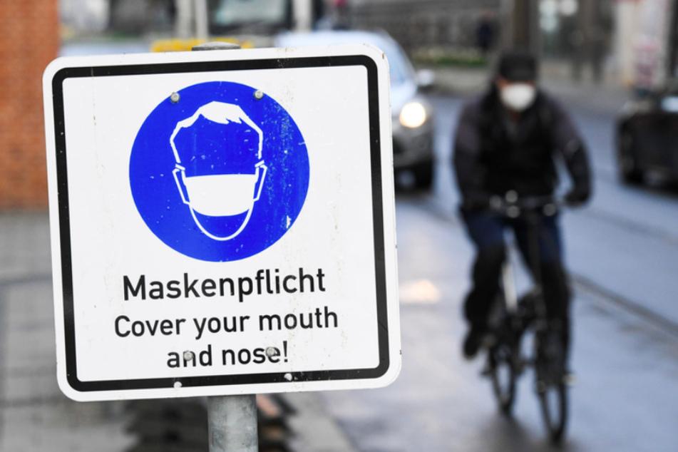 Ein Radfahrer fährt an einem Hinweisschild zur Maskenpflicht in der Münchner Innenstadt vorbei.