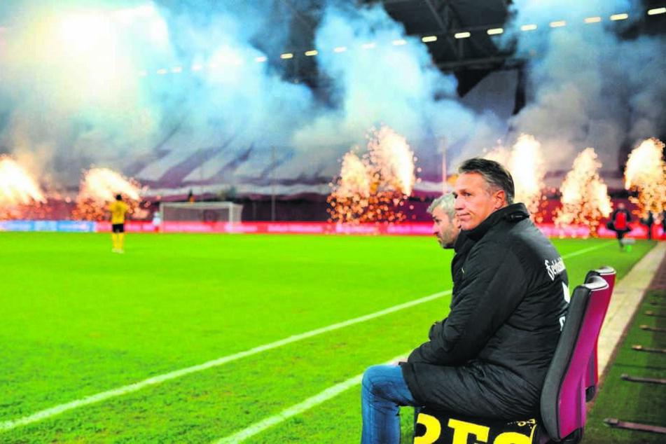 """Uwe Neuhaus auf der Trainerbank vor dem Heimspiel gegen den 1. FC Kaiserslautern. """"Hier im Osten leben die Menschen den Fußball"""", sagt er. Die Choreo im Hintergrund beweist das."""