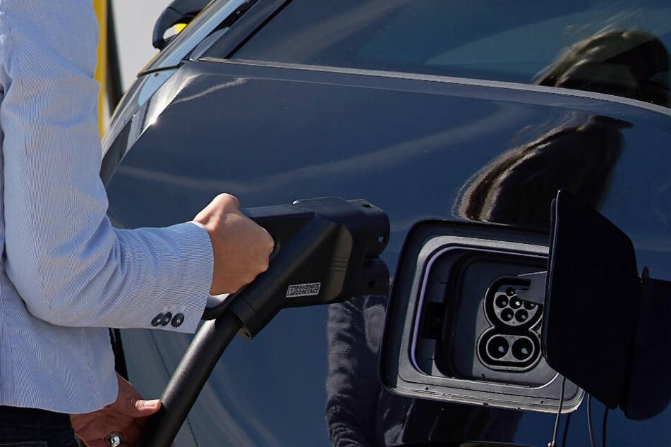 Eine Frau lädt ihr Elektroauto an einer Ultraschnellladestation auf.