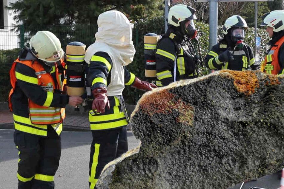 """Spezialeinsatzkräfte in Schutzmontur untersuchten das Paket. Im Vordergrund: das Gestein """"Uraninit"""" (Fotomontage)."""