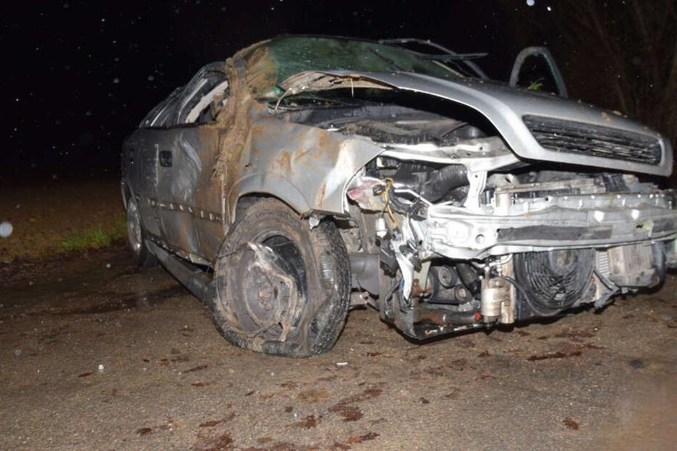 Junger Fahrer liegt nach schwerem Unfall neben seinem Auto, Anwohner ruft Hilfe