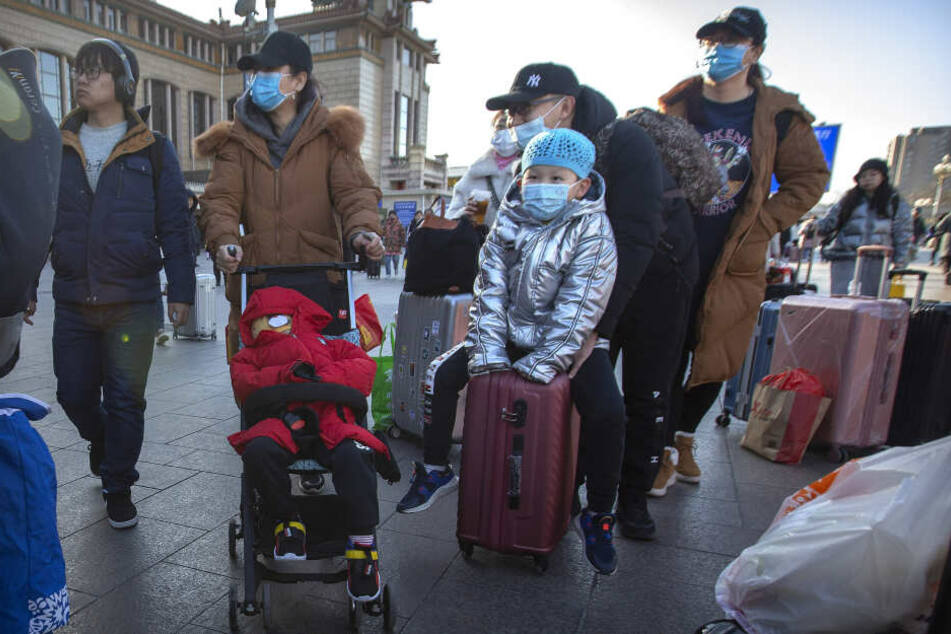 Reisende stehen mit Rollkoffern in der Nähe des Pekinger Bahnhofs und tragen Mundschutz.