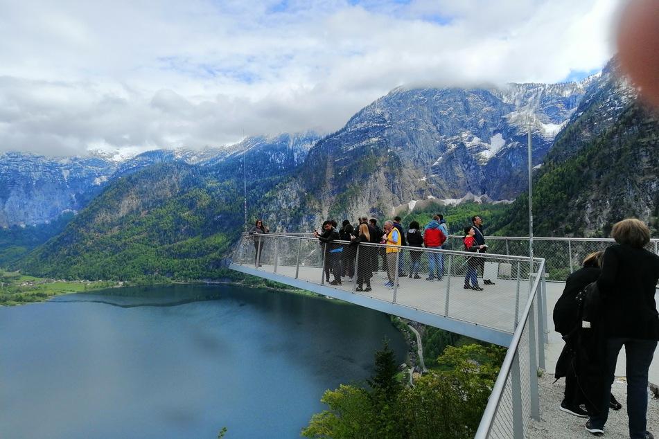Touristen stehen auf einer Aussichtsplattform über dem Hallstätter See.