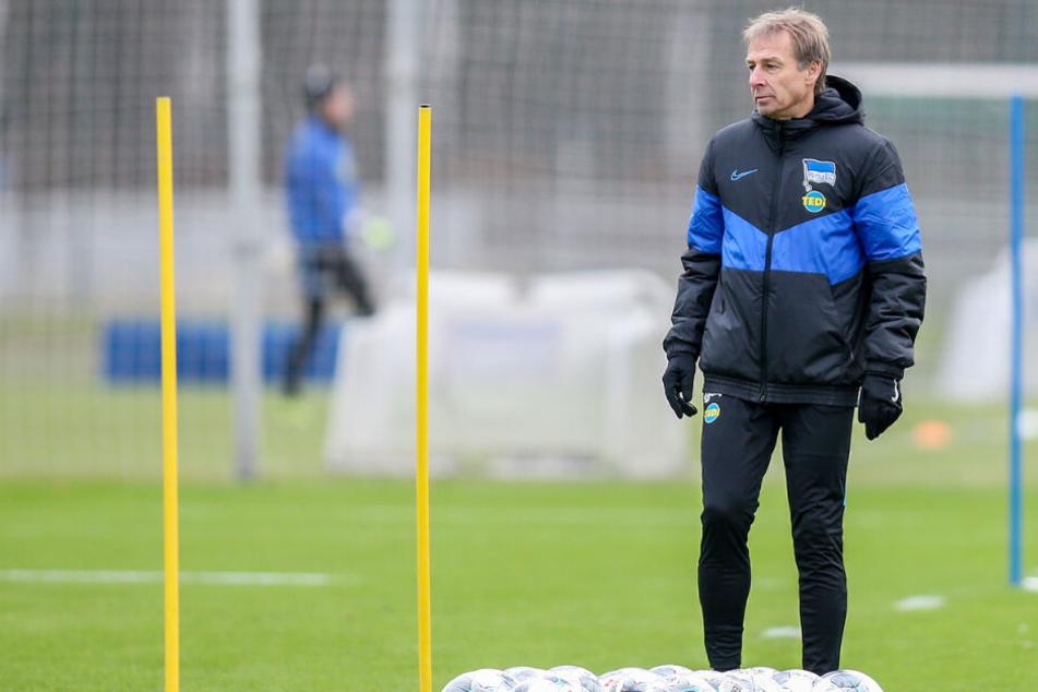 Herthas Trainer Jürgen Klinsmann steht hinter Fußbällen auf dem Trainingsplatz.