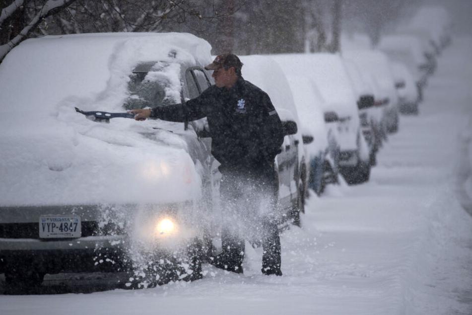 Ein Mann räumt Schnee von der Windschutzscheibe seines Autos bei dichtem Schneegestöber.