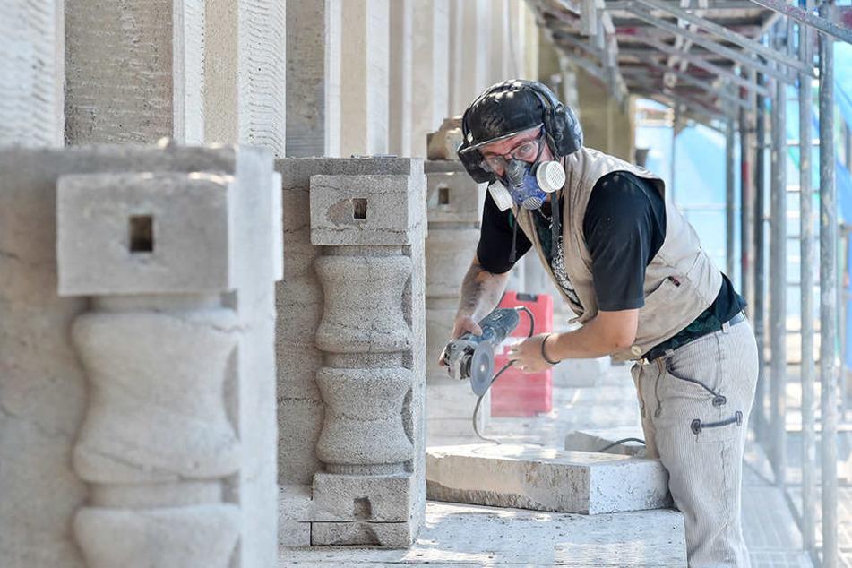 Steinmetz Lucas Noebel (22) tauscht defekte Steinplatten an der historischen Rathausfassade aus.