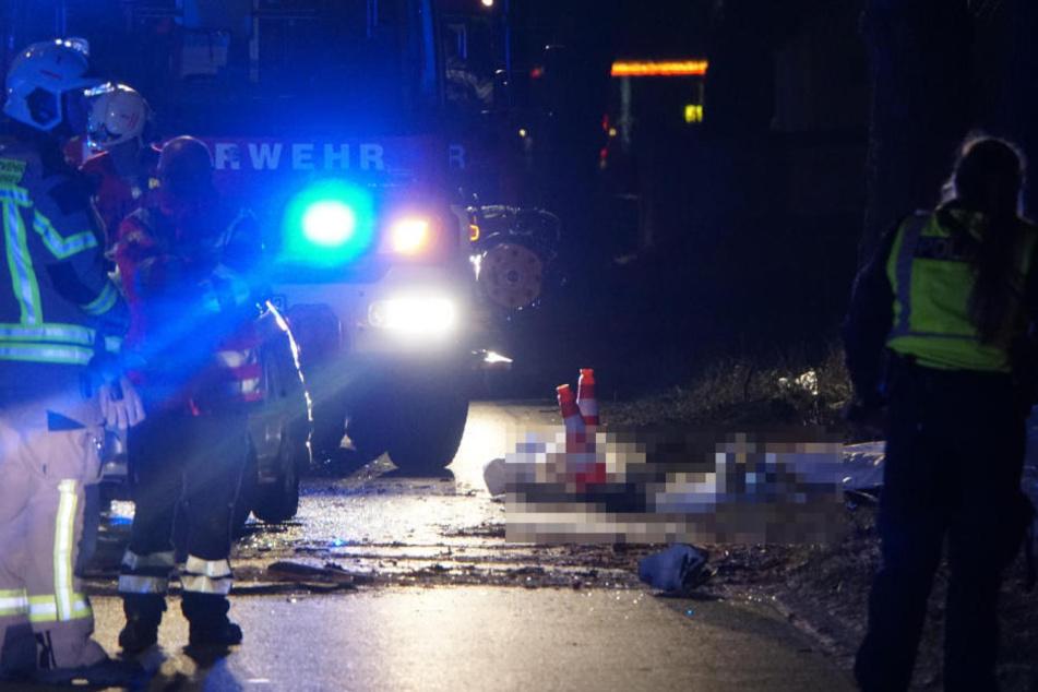 Die beiden Leichen liegen abgedeckt am Straßenrand.