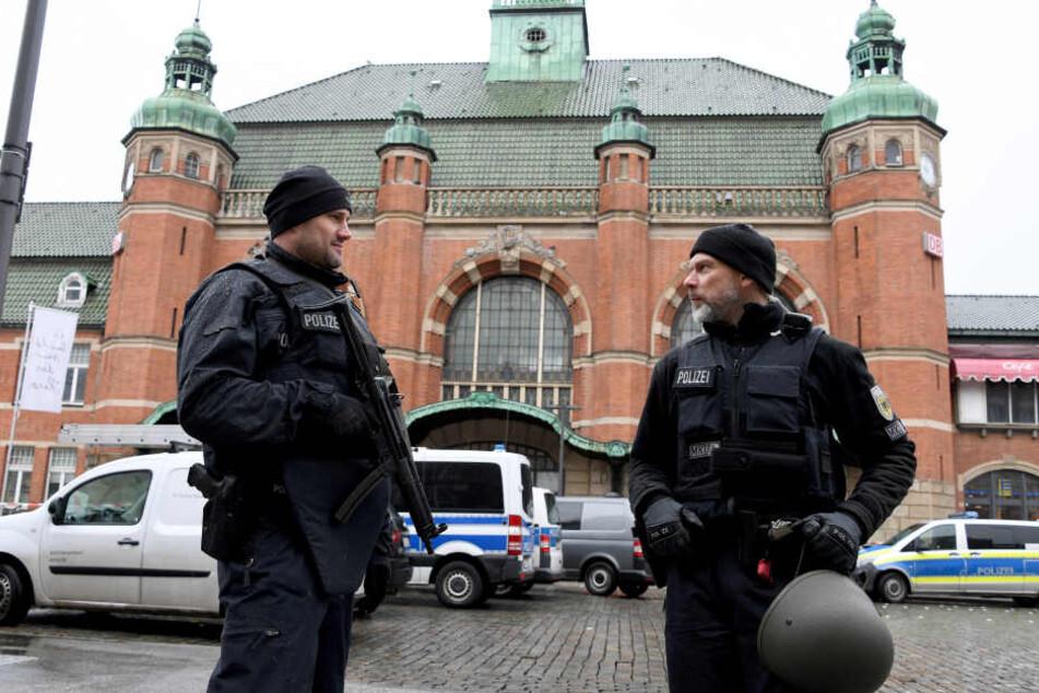 Polizeibeamte stehen vor dem Hauptbahnhof in Lübeck, der nach der Bombendrohung evakuiert werden musste.