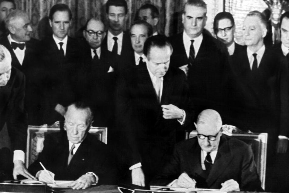 Der französische Staatspräsident Charles de Gaulle (r) und der deutsche Bundeskanzler Konrad Adenauer unterzeichnen am 22.1.1963 im Pariser Elysee-Palast den deutsch-französischen Freundschaftsvertrag.