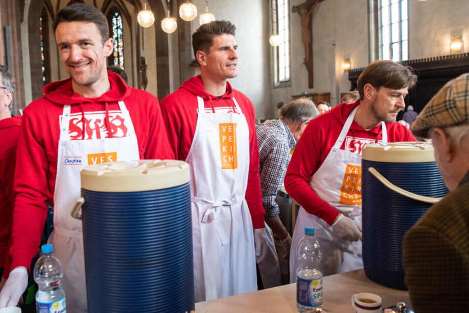 Christian Gentner (l-r), Mario Gomez und Co Trainer Wolfgang Beller verteilen Getränke an die Besucher der Vesperkirche.