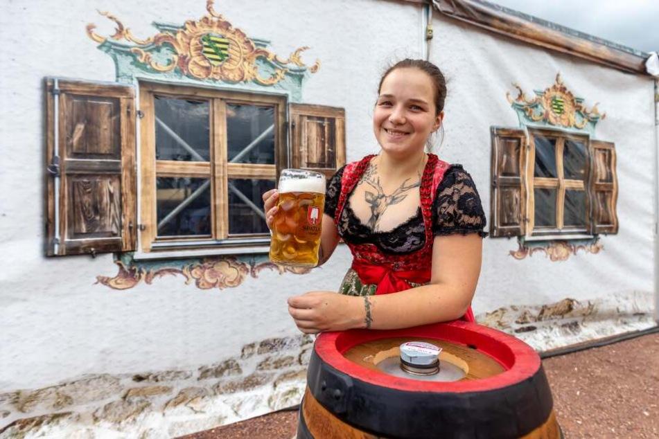 Service-Kraft Carolin (26) mit einer Maß Bier und einem Bierfass vor dem Festzelt.