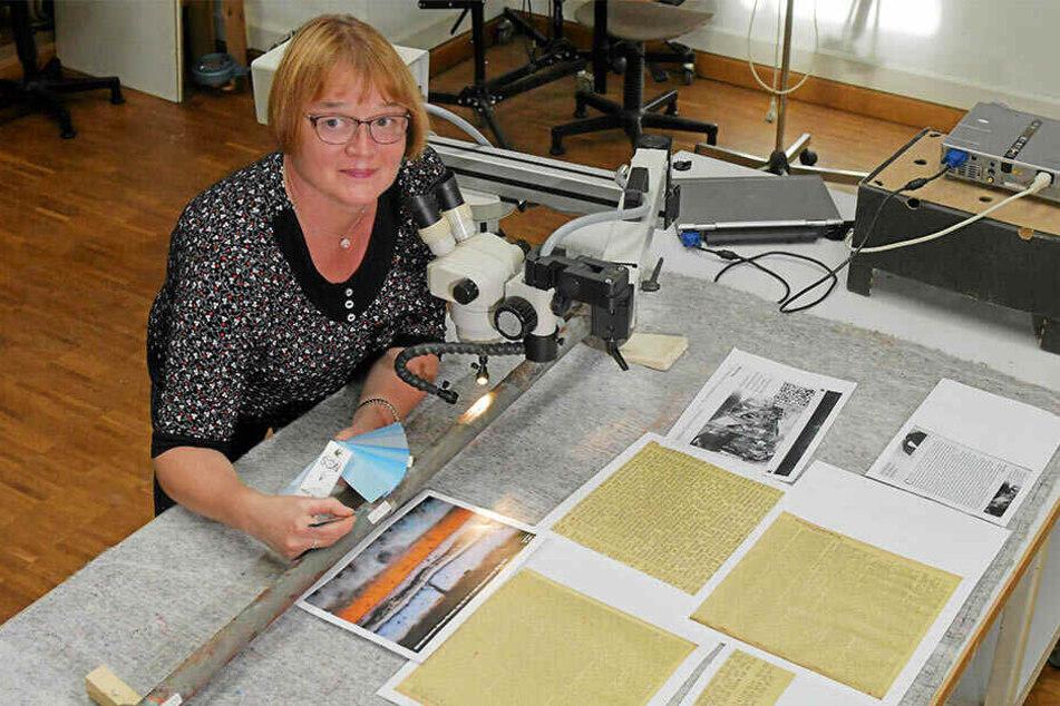 Metallrestauratorin Annegret Michel untersucht am Mikroskop einen historischen Pfeiler der Turmbekrönung.