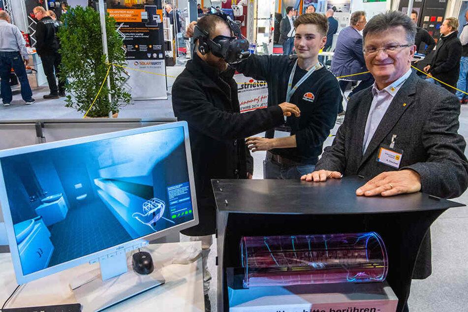 Carsten Tschirner schaut sich mit VR-Brille im virtuellen Haus um, Marvin Geisler (M.) und Robby Drechsel von der Elektroinnung erklären das System.