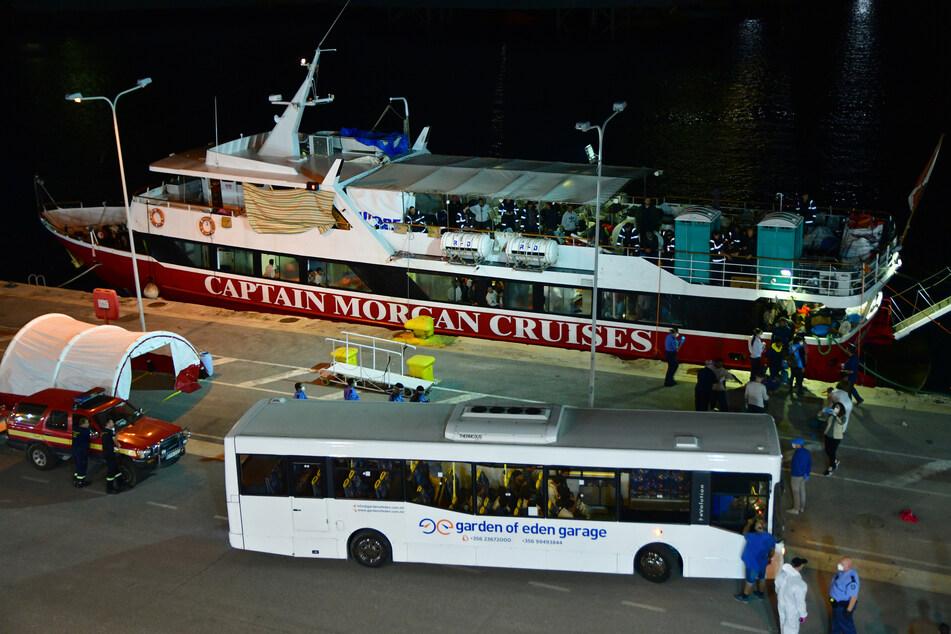 Migranten gehen in einem Hafen von Bord. Malta erlaubte rund 425 Migranten an Land zu gehen, nachdem sie mehr als einen Monat auf See waren.
