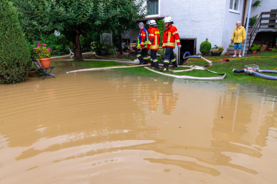 Mitglieder der Feuerwehr pumpen Wasser aus einem Garten ab nach starken Regenfällen in Oberbayern.