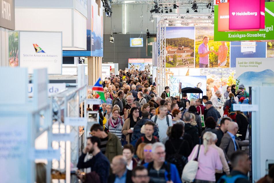 Besucher gehen bei der Reisemesse CMT durch eine Halle der Messe Stuttgart.