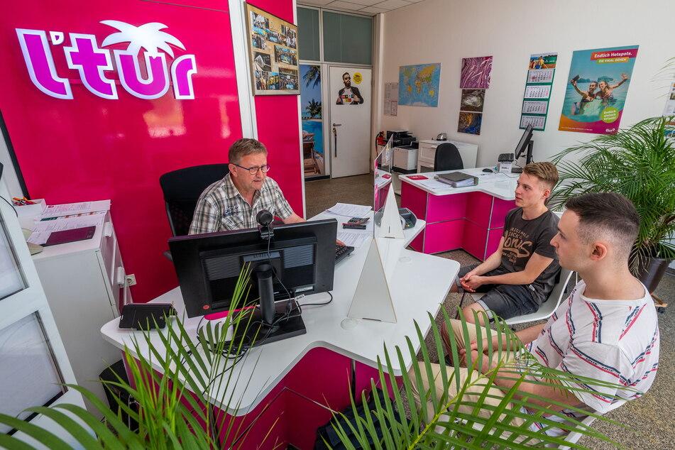 Peter Drahim (60, l.) vom L'tur Reisebüro sucht ein passendes Angebot für seine Kunden Daniel (19) und Florian (18, r.).