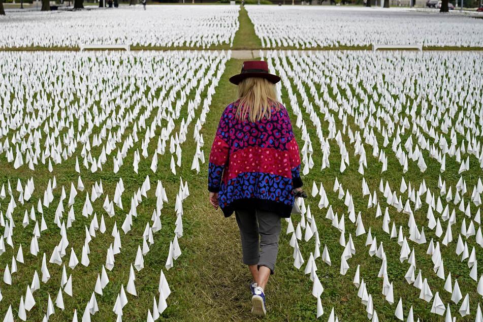 Die Künstlerin Suzanne Brennan Firstenberg geht durch ihre Kunstinstallation aus weißen Fänchen, die im Gedenken an die an COVID-19 verstorbenen US-Amerikaner in der Nähe des Robert F. Kennedy Memorial Stadiums in den Boden gesteckt wurden.