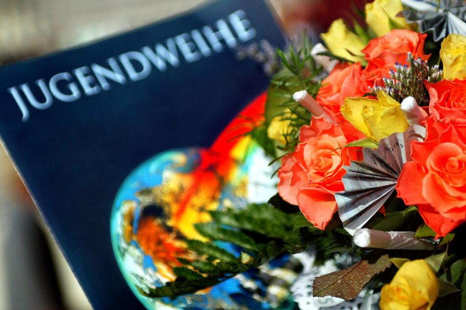 Eine Jugendweihe-Urkunde liegt neben einen Blumenstrauß.