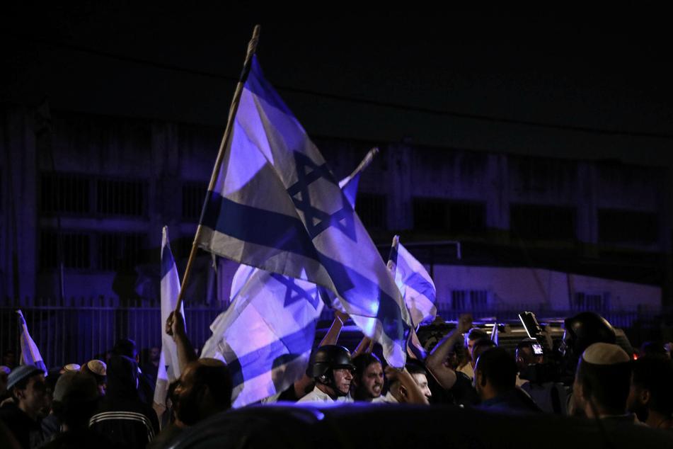 Jüdische Demonstranten schwenken israelische Flaggen während der nächtlichen Ausgangssperre in Lod.