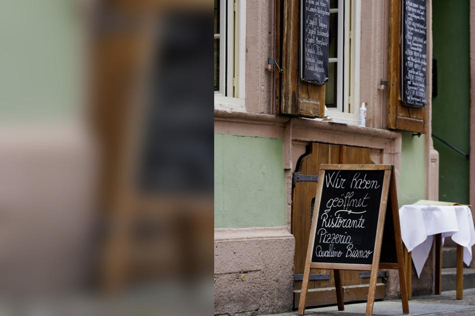 """Ein Schild mit der Aufschrift """"Wir haben geöffnet"""" steht vor der Essensausgabe eines Restaurants in der Heidelberger Innenstadt. (Archivbild)"""