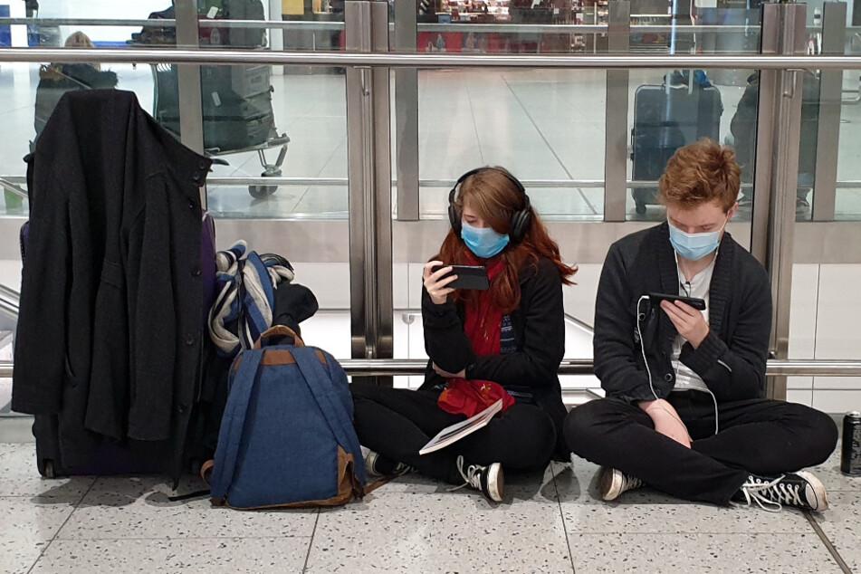 Passagiere sitzen am Flughafen Gatwick auf dem Boden. (Symbolbild)