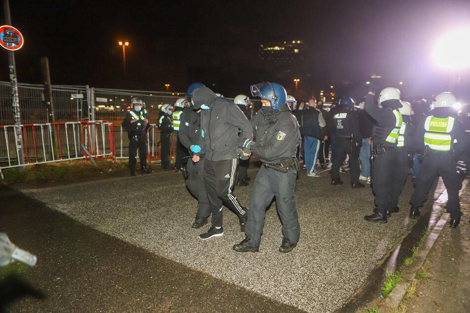 Die Polizei führt beim Millerntor-Stadion einen Mann ab. Am Freitagabend gab es eine Auseinandersetzung zwischen HSV- und St.-Pauli-Fans.