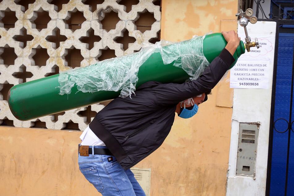 Ein Mann mit doppeltem Mundschutz trägt eine nachgefüllte Sauerstoffflasche auf dem Rücken. (Archivbild)