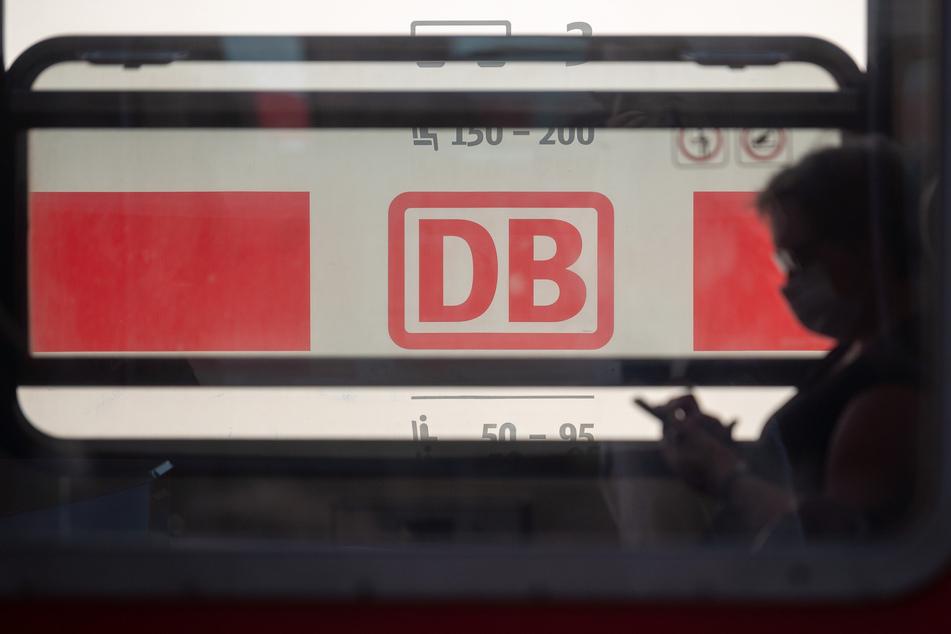 Ein Reisender mit Mund- und Nasenschutz sitzt in einem Zug der Deutschen Bahn, hinter dem ein ICE der Deutschen Bahn steht