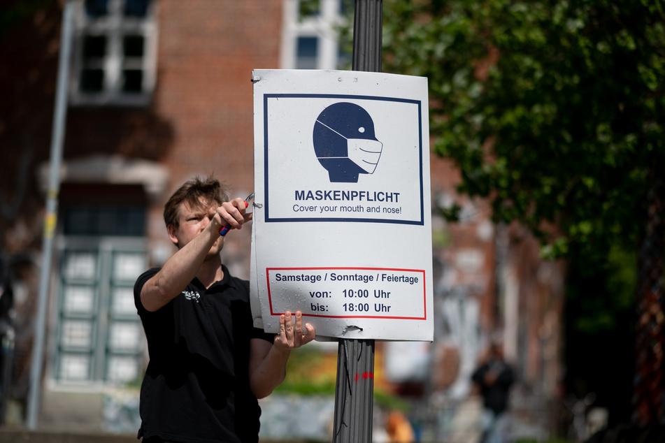 Ein Mitarbeiter hängt im Park Fiction in Hamburg ein Hinweisschild zur Maskenpflicht ab.