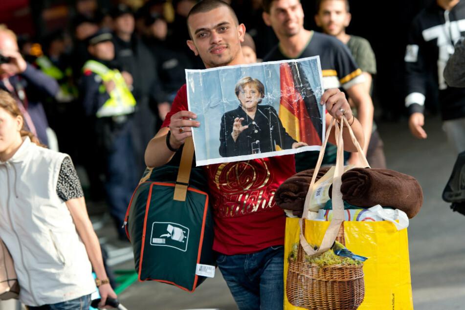 Ein Flüchtling, der kurz zuvor mit einem Zug angekommen ist, läuft 2015 auf dem Hauptbahnhof über den Bahnsteig und hält dabei ein Foto von Angela Merkel in den Händen. (Archivbild)