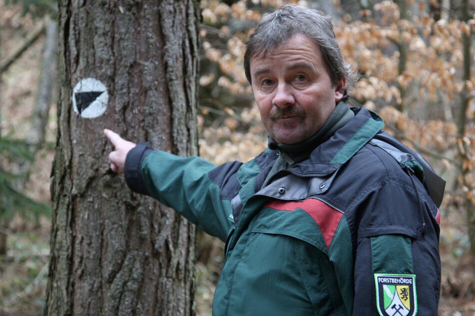Lutz Winkler (56), der zuständige Forst-Distriktleiter zeigt die offizielle Kennzeichnung des Kletterpfads am Kesselweg im Landschaftsschutzgebiet.