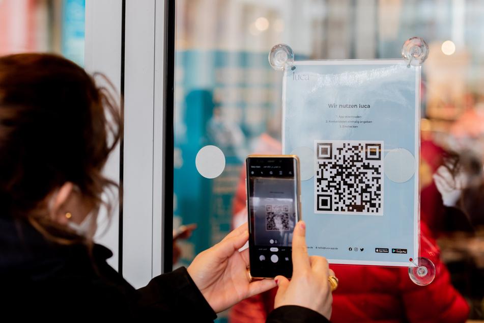 Eine Frau scannt am Eingang eines Bekleidungsgeschäftes einen QR-Code zum Download der Luca-App.