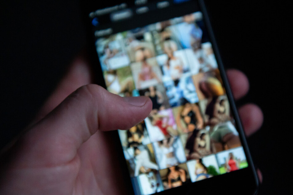 Ein Mann schaut sich auf einem Smartphone pornografische Bilder an. Ein Verdächtiger aus dem Kreis Erding, soll ein Mädchen zu Nacktfotos gedrängt haben. (Symbolbild)