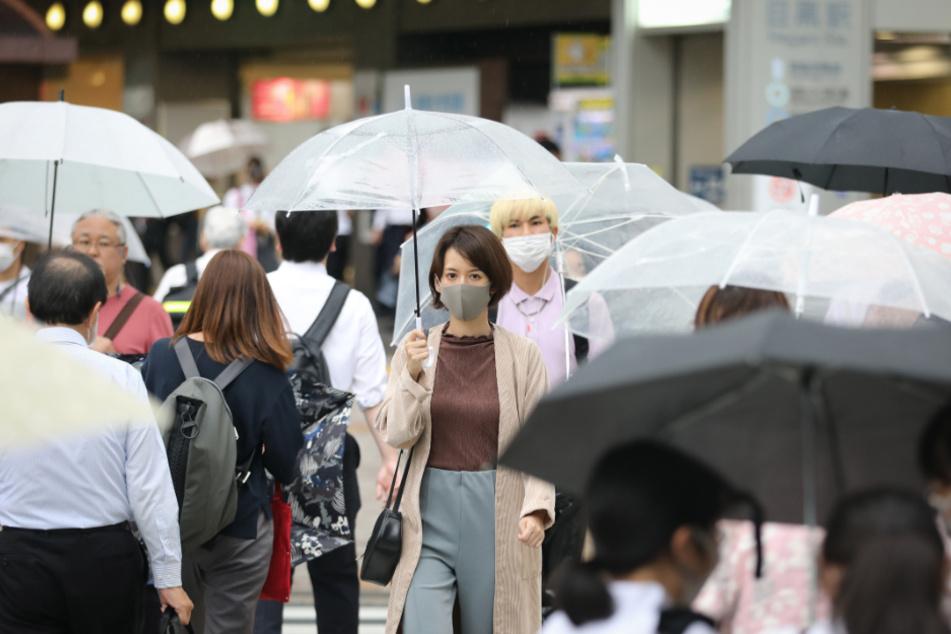 Tokio: Passanten mit Schutzmasken und Regenschirmen gehen über eine Straße. Landesweit wächst die Angst vor einer neuen Infektionswelle.
