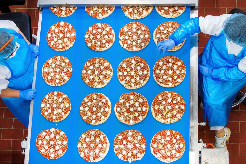 Mitarbeiterinnen kontrollieren in einem Pizzawerk die gleichmässige Verteilung des Belags auf Pizzen.