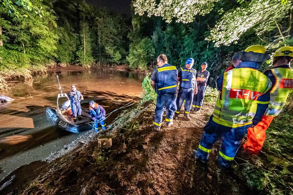 Rettungskräfte sichern einen Teich bei Fröndenberg dessen Deich durch sintflutartige Regenfällen aufgeweicht wurde und zu brechen droht.