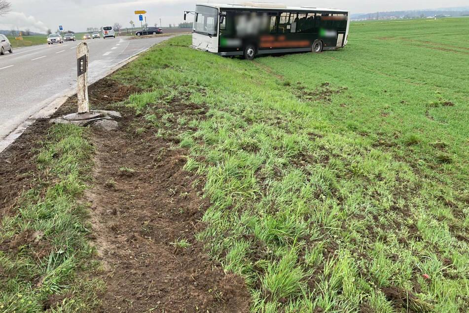 Der Bus steht auf einem Feld neben der Fahrbahn.
