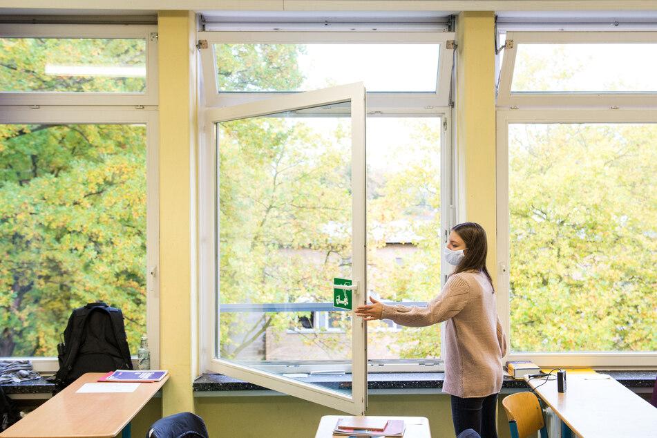 Eine Schülerin der Oberstufe öffnet das Fenster in einem Klassenraum.