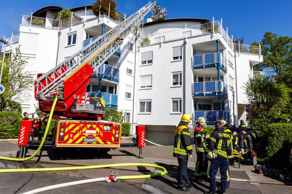 Einsatzkräfte der Feuerwehr stehen vor dem Wohnhaus in Bad Nauheim, in dem zwei männliche Leichen entdeckt wurden.