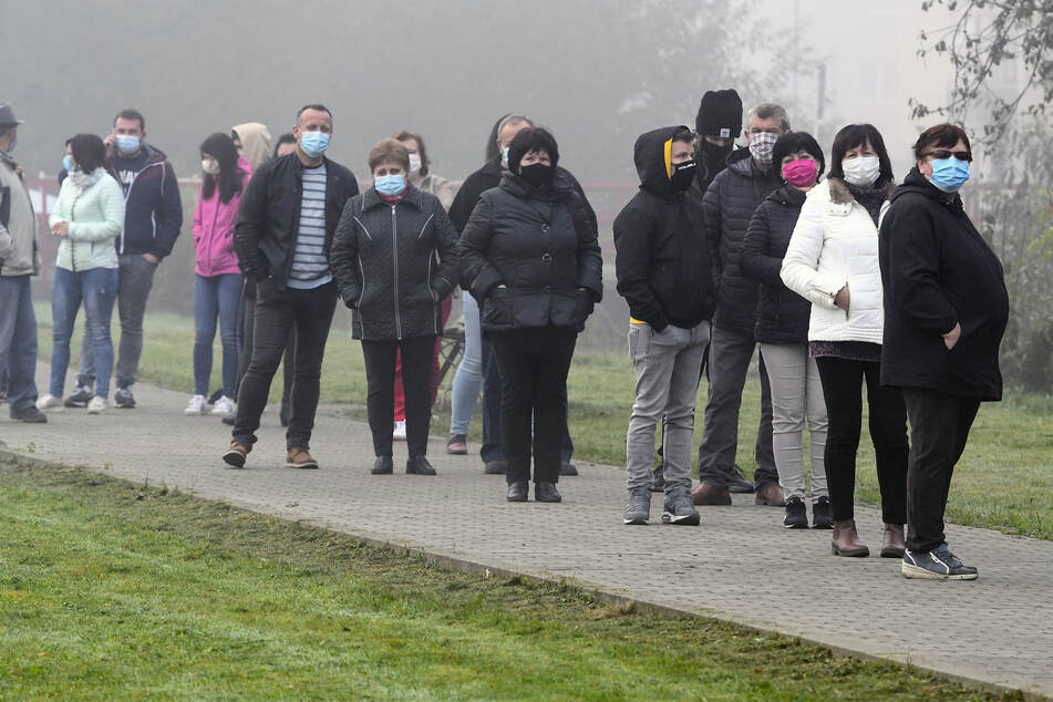 Menschen warten darauf im Dorf Raslavice im Bezirk Bardejov auf den Coronavirus getestet zu werden.