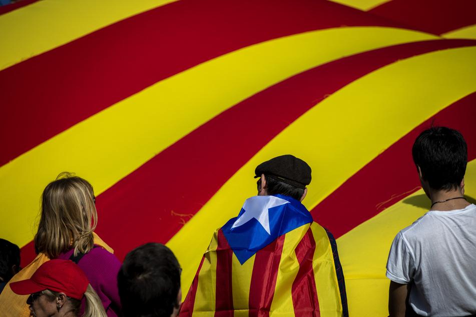 Teilnehmer eines Separatisten-Treffens des ehemaligen katalanischen Präsident Puigdemont stehen vor einer riesige Flagge der Unabhängigkeit Kataloniens.