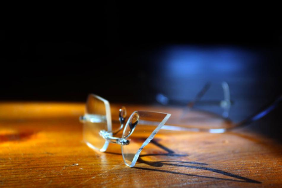 Eine zerbrochene Herrenbrille liegt auf dem Fußboden einer Wohnung. Beim Thema Gewalt gegen Männer schweigen viele, auch aus Scham. (Symbolbild)