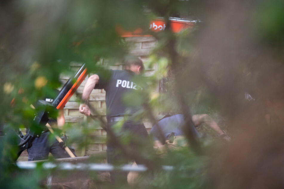 Niedersachsen, Seelze: Polizisten stehen mit Schaufeln neben einem Bagger in einer Kleingartenanlage in der Region Hannover.