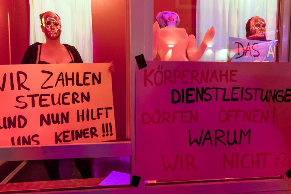"""Hamburg: Eine Prostituierte hält in der Herbertstraße ein Schild mit der Aufschrift """"Wir zahlen Steuern und nun hilt uns keiner!"""". Sie demonstriert mit anderen Frauen für die Öffnung der Bordelle auf St. Pauli."""