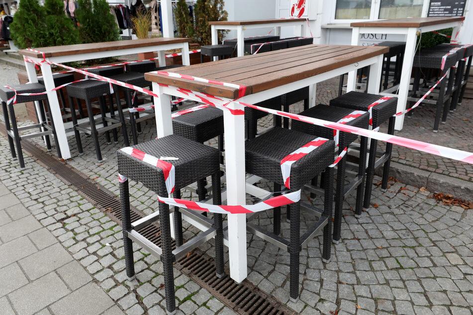 Mit rot-weißem Flatterband abgesperrt sind die Sitzgelegenheiten vor einer gastronomischen Einrichtung. (Symbolbild)